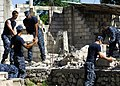 US Navy 100127-N-5244H-053 Sailors assigned to the amphibious dock landing ship USS Carter Hall (LSD 50) remove rubble from a home during a community relations (COMREL) project.jpg