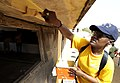 US Navy 100409-N-7948C-080 Logistics Specialist 2nd Class Evonne Hill paints the outside walls of a classroom at Pikine17A and HLM elementary school during a community outreach project in Pikine.jpg