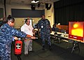 US Navy 100527-N-8241M-002 Culinary Specialist 2nd Class Cora Udell, assigned to the U.S. Navy Hospital Guantanamo Bay, operates a CO2 fire extinguisher simulator at the Naval Station Guantanamo Bay, Cuba bi-annual Safety Stand.jpg
