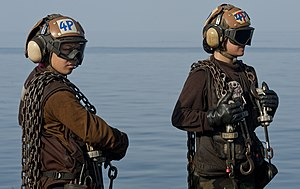 US Navy 120107-N-OY799-205 Plane captains from the Golden Dragons of Strike Fighter Squadron (VFA) 192 stand by during aircraft recovery operations.jpg