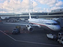 """United Airlines Airbus A320 painted in the retro """"United Friend Ship"""" livery at the gate at SFO Airport."""