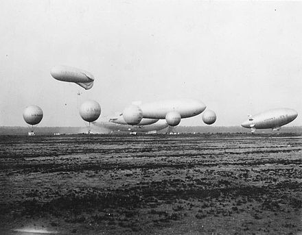 "U.S. Navy airships and balloons, 1931: in the background, ZR-3, in front of it, (l to r) J-3 or 4, K-1, ZMC-2, in front of them, ""Caquot"" observation balloon, and in foreground free balloons used for training. Usn-airships.jpg"
