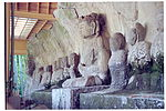 Photograph of a row of ca. ten seated stone statues in front of a rock. Three-quarter view. One of the statues is about twice as large as the others.