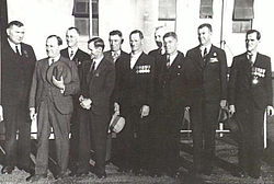 A group of ten men wearing suits and military medals gathered together outside of a building.