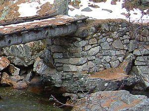 Masonry - Dry set masonry supports a rustic log bridge, where it provides a well-drained support for the log (which will increase its service life).