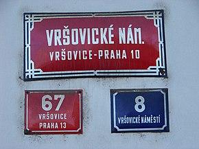 Trois plaques de rues: l'une en haut, très grande, horizontale et rouge indique le nom de la rue, ainsi que celui du quartier et de l'arrondissement; en dessous, une petite plaque rouge mentionne un numéro, le nom du quartier et d'un autre arrondissement; à sa droite, une autre petite plaque bleue indique un autre numéro et le nom de la rue.