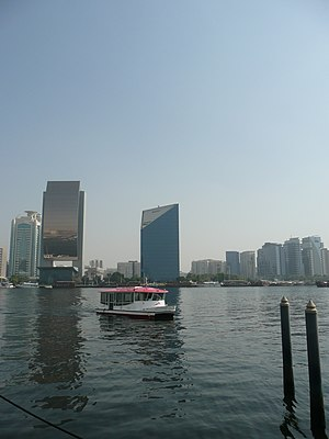 Dubai Creek - Water bus in Dubai Creek, with the National Bank of Dubai and the Dubai Chamber buildings in the background