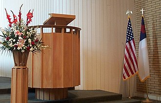 Civil religion - The Christian flag displayed alongside the flag of the United States next to the pulpit in a church in California.  Note the eagle and cross finials on the flag poles.