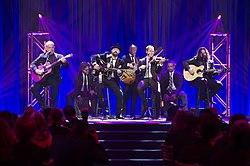 Группа из семи мужчин в темных костюмах, играющих на различных музыкальных инструментах на сцене перед публикой.