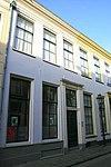 foto van Pand met gepleisterde gevel, rechte lijst en voordeur en bovenlicht in pilasteromlijsting