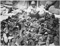 """Pfc. Robert Askew...with the 3278th Quartermaster Company, examines overshoes which have been turned in. Overshoes prov - NARA - 531412.tif"