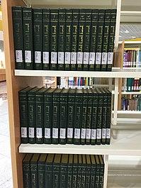 صورة لكتب ذات لون متجانس أخضر غامق مصفوفة بجانب بعضها البعض فوق ثلاثة رفوف