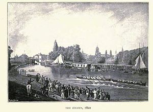 A river scene, with two eight-oared boats racing in the middle of the river, one just in front of the other. There are crowds on each bank and some sailing boats and barges by the far bank. In the distance, trees and church spires.