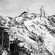 The snow covered ridgeline of a steep hill running away from the camera and sloping downwards from left to right. In the bottom left foreground two soldiers with machine-guns stand in a trench in front of a defensive position constructed of sandbags and logs, facing downhill. In the background several trees, stripped of foliage, stand on crest.