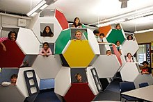 Brightly colored stacked truncated octahedrons with children's faces in the openings
