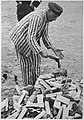A prisoner splits wood at Sachsenhausen.jpg