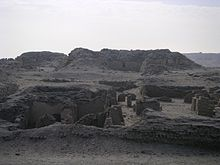 A maze of low walls and ruins in the desert.