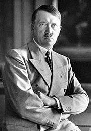 Photo portrait noir et blanc d'Adolf Hitler en costume deux pièces clair, assis de face, les bras croisés sur son ventre.