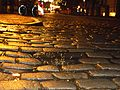After rain in winter evening, wet cobblestone street Steinweg Marburg (Germany) with bicycle and reflection of lights in a puddle 2017-01-04.jpg