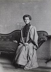 Olga Boznańska siedząca na kanapie z papierosem w dłoni