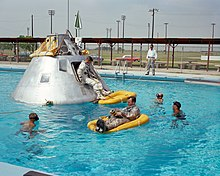 The Apollo spacecraft and orange rafts float in a pool, surrounded by divers