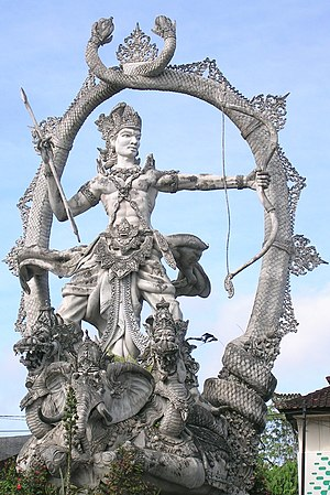 Vana Parva - Aranya Parva dedicates many chapters on Arjuna (pictured above in Bali, Indonesia). Arjuna visits heaven, meets Indra and other deities, receives celestial weapons as gifts. When he returns to the forest home of Pandava brothers, he demonstrates to them their power by destroying an aerial city. Sage Narada appears, demands to know why he is wrongly unleashing weapons of war without cause, just to show off. Arjuna stops the violence.