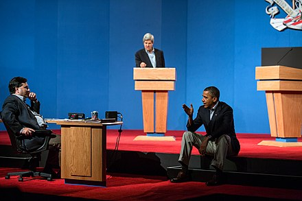 President Obama talks with Ron Klain during presidential debate preparations. Senator John Kerry, at podium, played the role of Mitt Romney during the preparatory sessions. Barack Obama presidential debate preparations.jpg