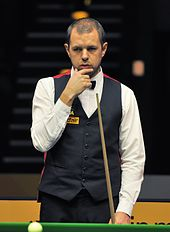 Barry Hawkins stands holding his chine with his right hand and a cue in his left hand looking at a table.