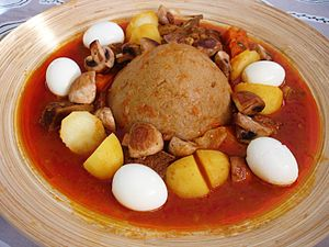 Libyan cuisine - Bazin (center) served with a stew and whole hard-boiled eggs