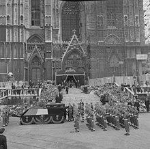 le cercueil de la reine est posé sur un affût de canon drapé du drapeau belge et tiré par des militaires devant la façade de la cathédrale recouverte en partie d'échafaudages et dont l'entrée en ornée d'un dais de tissu sombre