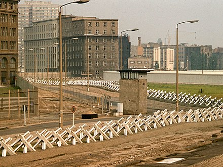 "This section of the Wall's ""death strip"" featured Czech hedgehogs, a guard tower and a cleared area, 1977. Berlin Wall death strip, 1977.jpg"