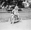 Blond kindje op Mickey Mouse hobbelpaard in Suriname, Bestanddeelnr 252-6874.jpg