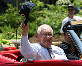 An elderly almost-bald man wearing a striped button-up shirt and a tie adorned with a pattern of baseballs waves a cap from a convertible.