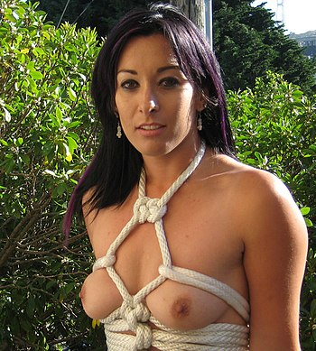 English: A model with bound breasts, in a karada body harness.