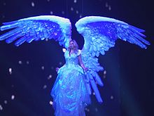 A female blond performer. She is wearing a white winged dress and sings as she's lifted in the air.
