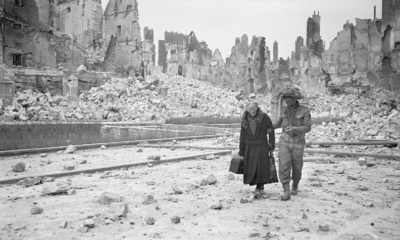 A soldier holding the arm of an elderly lady in a debris-strewn street, with ruined buildings in the background
