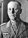 The head and shoulders of an elderly man, shown in semi-profile. He wears a peaked cap and a military uniform with an Eagle above his right and various military decorations above left breast pocket, and an Iron Cross displayed at the front of his shirt collar. His facial expression is a determined; his eyes are looking into the distance to the left of the camera.