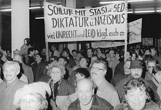 Stasi - Citizens protesting and entering the Stasi building in Berlin; the sign accuses the Stasi and SED of being Nazi-like dictators. 1990.