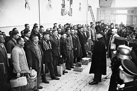 The Dachau concentration camp was created for the purpose of holding political opponents. In time for Christmas of 1933, roughly 600 of the inmates were released as part of a pardoning action. The picture above depicts a speech by camp commander Theodor Eicke to prisoners who were about to be released. Bundesarchiv Bild 183-R96361, Dachau, Konzentrationslager.jpg
