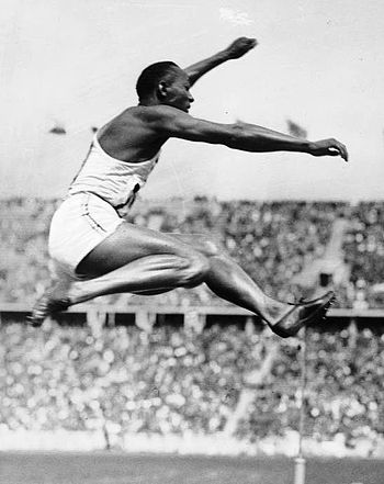 Owens performing the long jump at the Olympics.