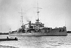 A large battleship lined with guns and equipped with two tall masts sits in harbor.