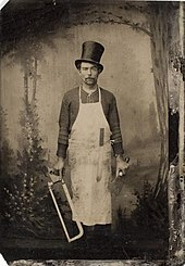 A man wearing an apron and holding two saws