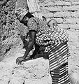 COLLECTIE TROPENMUSEUM Een Samo vrouw met kind op de rug maalt het graan tussen twee stenen TMnr 20010226.jpg