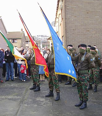 Irish National Liberation Army - INLA volunteers carrying a flag of Ireland, a red flag and a Starry Plough flag in the Bogside area of Derry (2005)