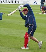 A man wearing dark blue shorts and sweat-shirt with a large red pad fastened to his left leg holds a cricket bat in front of him.