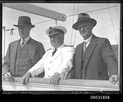 Captain and two passengers on deck of SS RUNIC, 1920s (8114423517).jpg