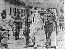 Two Dutch men enter an internment camp, one in a white suit and the other in a military uniform