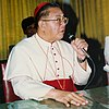 Jaime Cardinal Sin of the Philippines shown wearing a white cassock with a red belt and skullcap holding a microphone