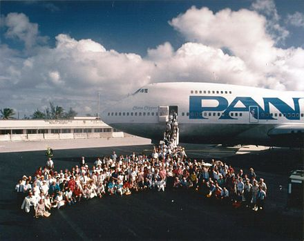 "Passengers and crew of Pan Am's China Clipper II Boeing 747 pose for a ""class picture"" at Wake Island during a 1985 trip across the Pacific to commemorate the 50th anniversary of the first China Clipper flight. China Clipper II at Wake Island 1985.jpg"