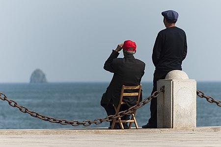 Dalian, Liaoning, China: Two elderly Chinese guys enjoying the sea at Xinghai Bay